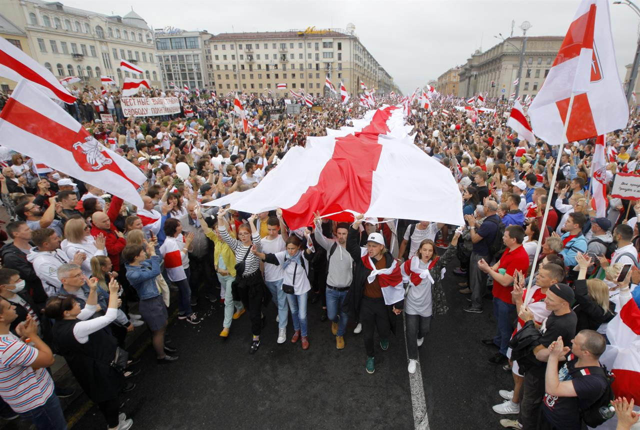 FILE - In this Sunday, Aug. 23, 2020 file photo, demonstrators carry a huge historical flag of Belarus as thousands gather for a protest at the Independence square in Minsk, Belarus. Belarus President Alexander Lukashenko has relied on massive arrests and intimidation tactics to hold on to power despite nearly three months of protests sparked by his re-election to a sixth term, but continuing protests have cast an unprecedented challenge to his 26-year rule. (AP Photo/Dmitri Lovetsky, File)
