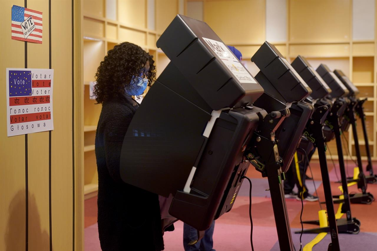 A woman casts her ballot on the first day of early voting in a recently-shuttered store at Oak Park Mall Saturday, Oct. 17, 2020, in Overland Park, Kan. (AP Photo/Charlie Riedel, File)