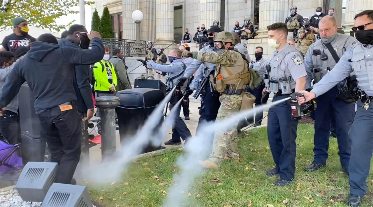 In this image taken from video, Alamance County sheriff's deputies use pepper spray on a crowd of protesters outside the courthouse in Graham, N.C., Saturday, Oct. 31, 2020. A get-out-the vote rally that ended with North Carolina police pepper spraying and arresting attendants was the result of participants blocking the roadway without authorization, authorities said Saturday. (Carli Brosseau/The News & Observer via AP)