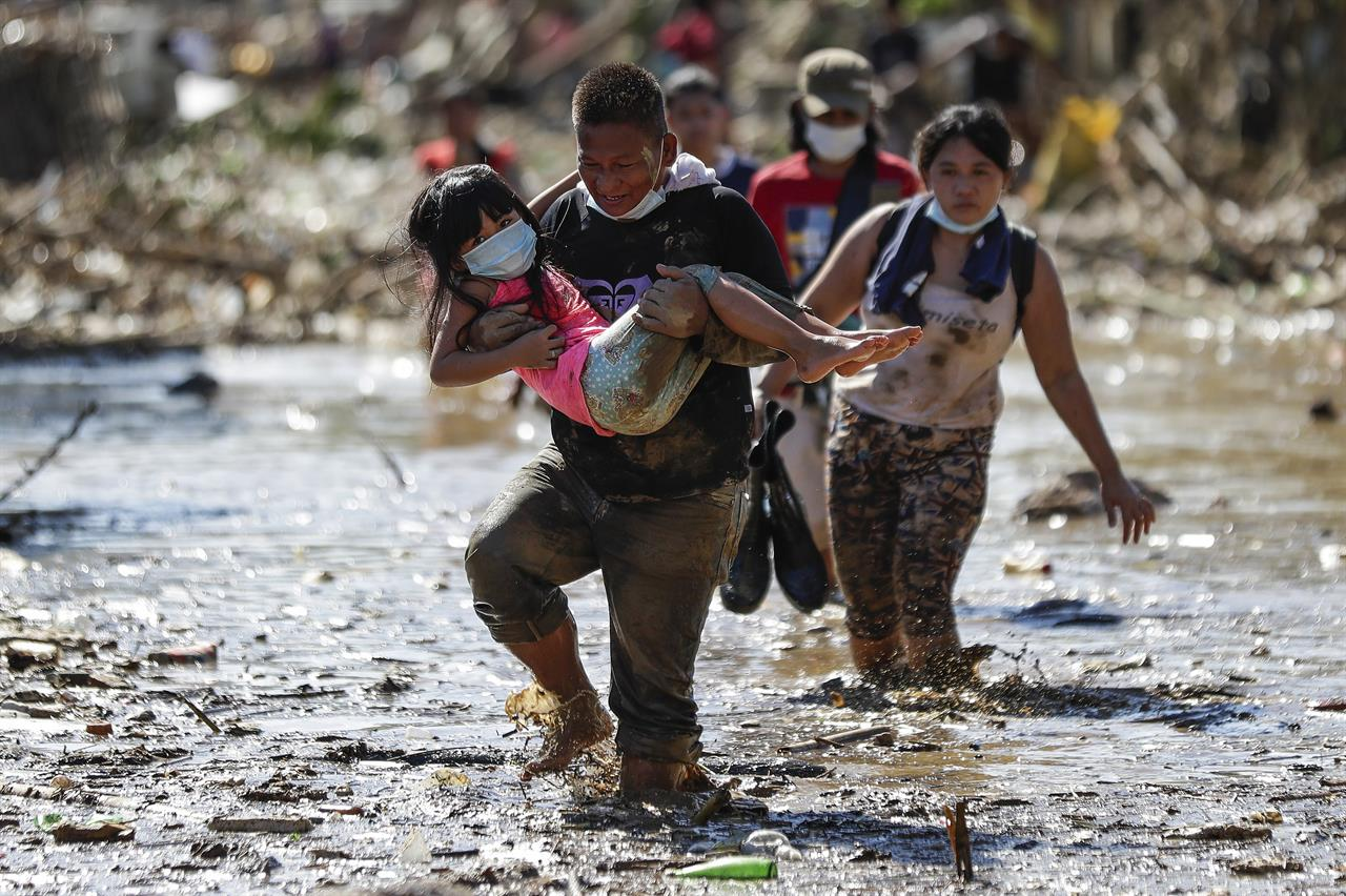 A man carries a girl through debris and floods in the typhoon-damaged Kasiglahan village in Rodriguez, Rizal province, Philippines, Friday, Nov. 13, 2020. Thick mud and debris coated many villages around the Philippine capital Friday after Typhoon Vamco caused extensive flooding that sent residents fleeing to their roofs and killing dozens of people. (AP Photo/Aaron Favila)