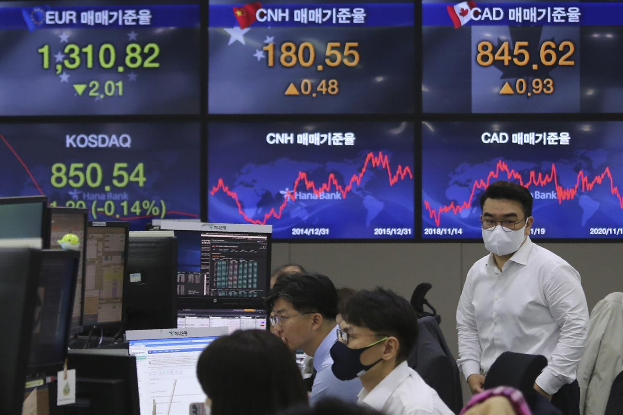 A currency trader passes by screens showing foreign exchange rates at the foreign exchange dealing room of the KEB Hana Bank headquarters in Seoul, South Korea, Thursday, Nov. 19, 2020. Asian stocks followed Wall Street lower on Thursday as anxiety about the economic fallout from rising coronavirus infections in the United States and Europe clashed with optimism about a possible vaccine. (AP Photo/Ahn Young-joon)