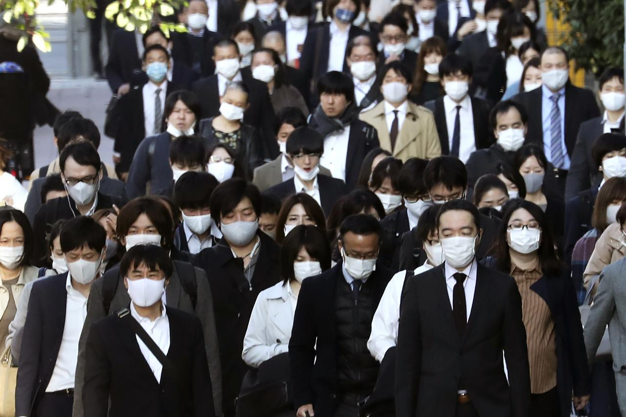 Commuters wearing face masks to protect against the spread of the coronavirus walk along a pedestrian sidewalk in Tokyo, Tuesday, Nov. 17, 2020. (AP Photo/Koji Sasahara)