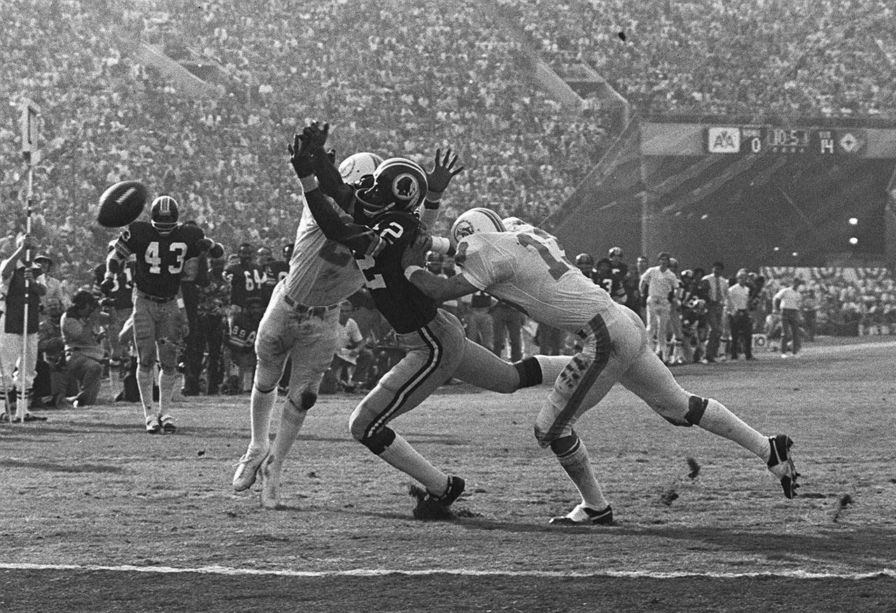 FILE - In this Jan. 14, 1973, file photo, Miami Dolphins' Lloyd Mumphord, left, and Jake Scott (13) break up a pass to Washington Redskins' Charley Taylor near the goal line to stop a Redskins drive during NFL football's Super Bowl 7 in Los Angeles. Scott, the star safety who was the most valuable player in the Super Bowl that completed the Dolphins' 1972 perfect season, died Thursday, Nov. 19, 2020, in Atlanta. He was 75. Scott died after a fall down a stairway that left him in a coma, former teammate Dick Anderson said. (AP Photo, File)