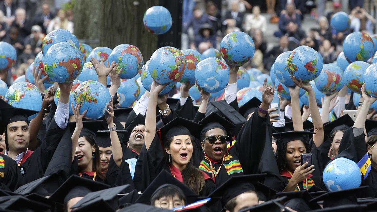 FILE— In this May 30, 2019 file photo, graduates of Harvard's John F. Kennedy School of Government hold aloft inflatable globes as they celebrate graduating during Harvard University's commencement exercises in Cambridge, Mass. A petition circulating at Harvard University demands that school officials create new accountability standards for former Trump administration officials who seek to work or speak on campus, an idea that has drawn outrage from prominent conservatives. (AP Photo/Steven Senne, File)