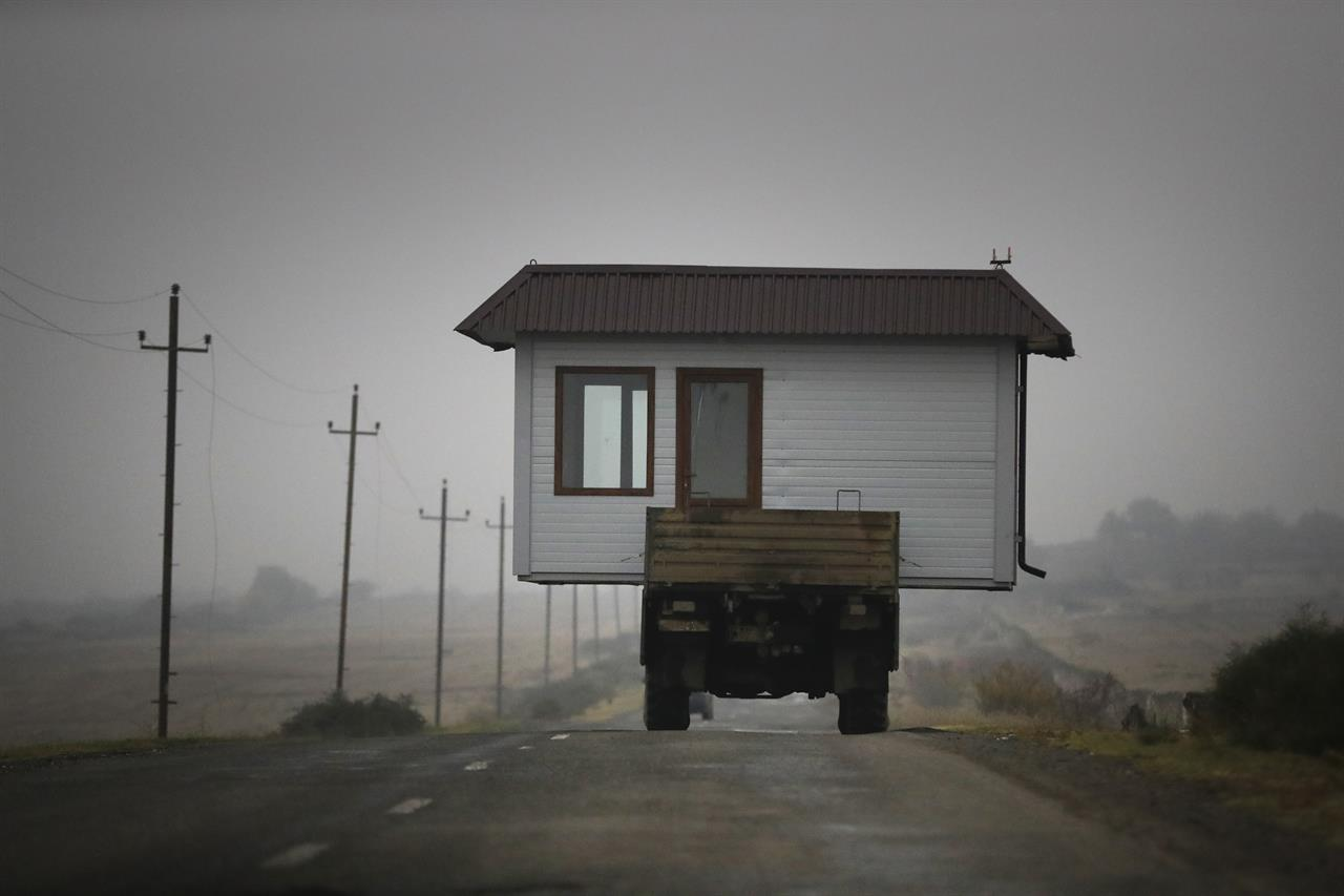 A family drives a truck loaded with a small house along a highway as they leave their home village in the separatist region of Nagorno-Karabakh, Wednesday, Nov. 18, 2020. A Russia-brokered cease-fire to halt six weeks of fighting over Nagorno-Karabakh stipulated that Armenia turn over control of some areas it holds outside the separatist territory's borders to Azerbaijan. Armenians are forced to leave their homes before the region is handed over to control by Azerbaijani forces. (AP Photo/Sergei Grits)