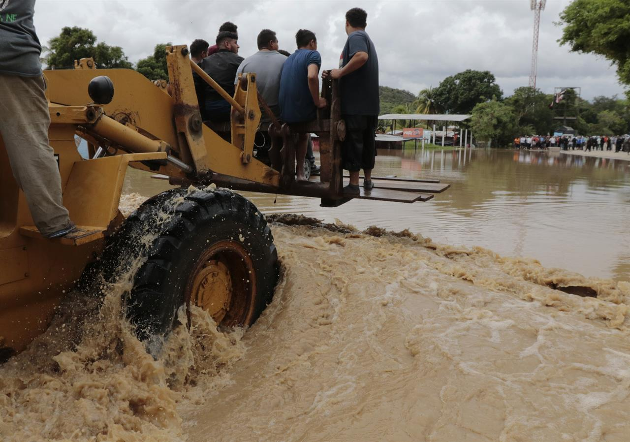 A heavy lifter carries people across a flooded area after the passing of Hurricane Iota in La Lima, Honduras, Wednesday, Nov. 18, 2020. Iota flooded stretches of Honduras still underwater from Hurricane Eta, after it hit Nicaragua Monday evening as a Category 4 hurricane and weakened as it moved across Central America, dissipating over El Salvador early Wednesday. (AP Photo/Delmer Martinez)