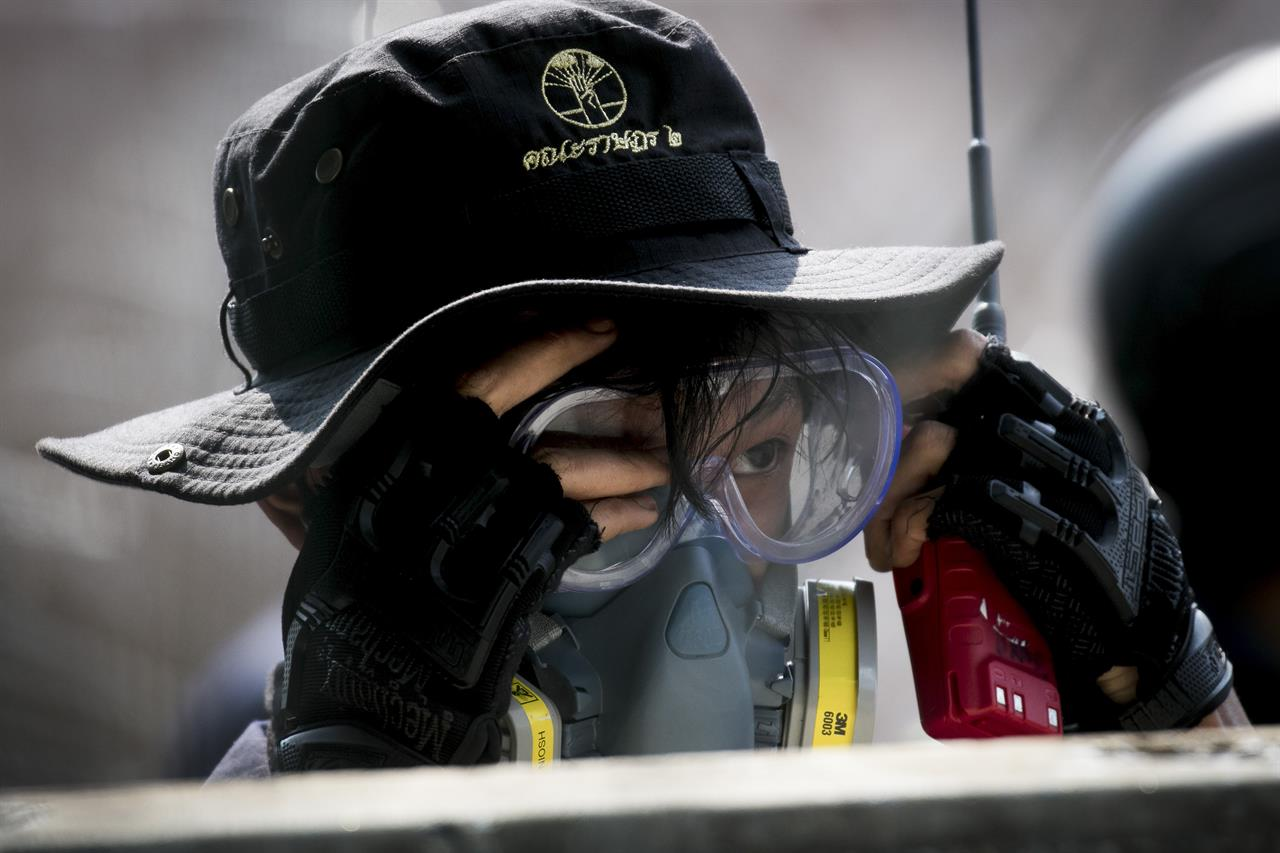 A pro-democracy demonstrator puts on googles during clashes with riot police near the Parliament in Bangkok, Tuesday, Nov. 17, 2020. Thailand's political battleground shifted to the country's Parliament Tuesday, where lawmakers are considering proposals to amend the country's constitution, one of the core demands of the student-led pro-democracy movement. (AP Photo/Wason Wanichakorn)