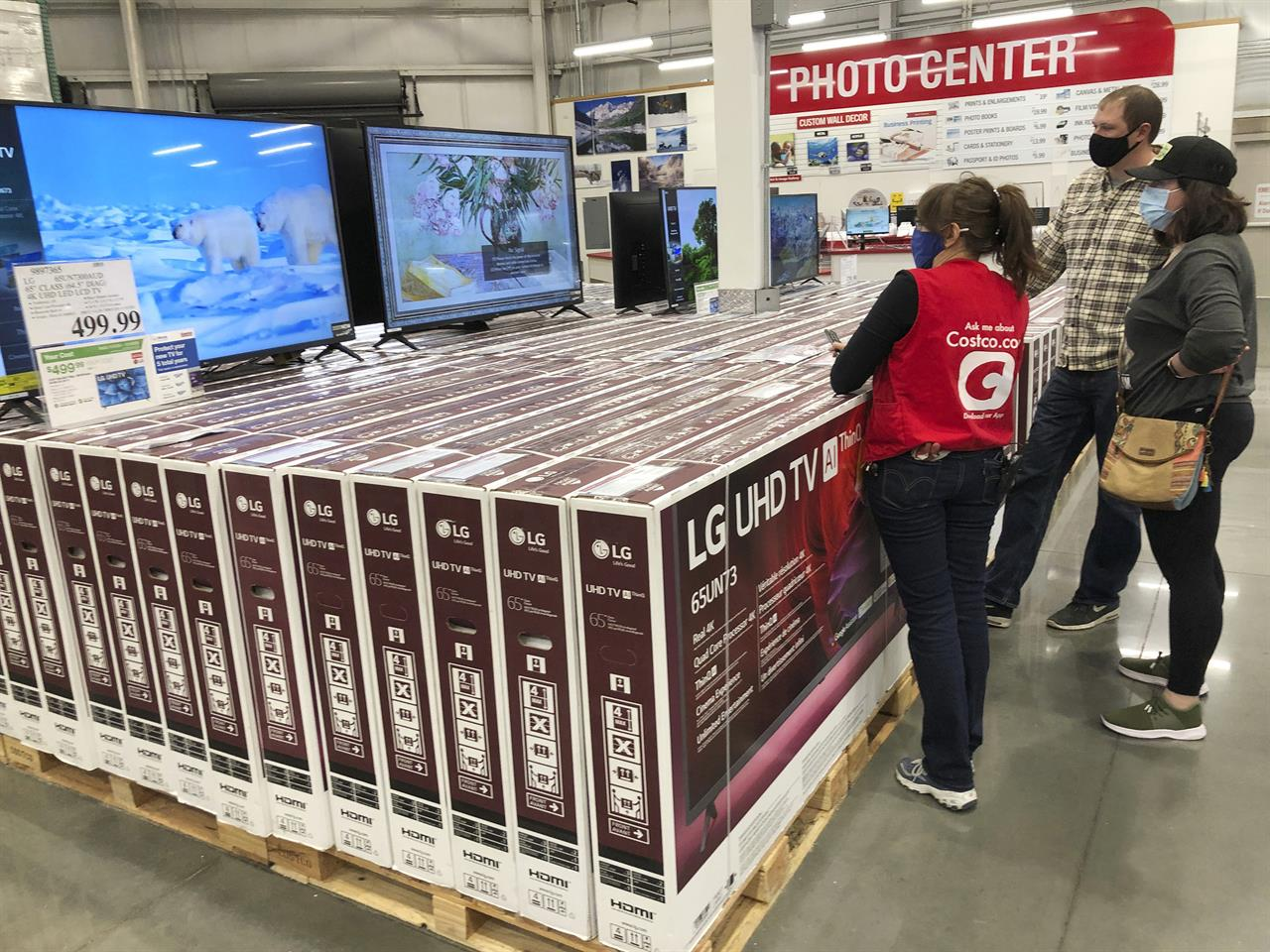 A sales associate helps customers as they consider the purchase of a big-screen television at a Costco warehouse on Wednesday, Nov. 18, 2020, in Sheridan, Colo.  U.S. consumer confidence fell to a reading of 96.1 in November as rising coronavirus cases pushed Americans' confidence down to the lowest level since August. The Conference Board said the November reading represented a drop from a revised 101.4 in October.  (AP Photo/David Zalubowski)