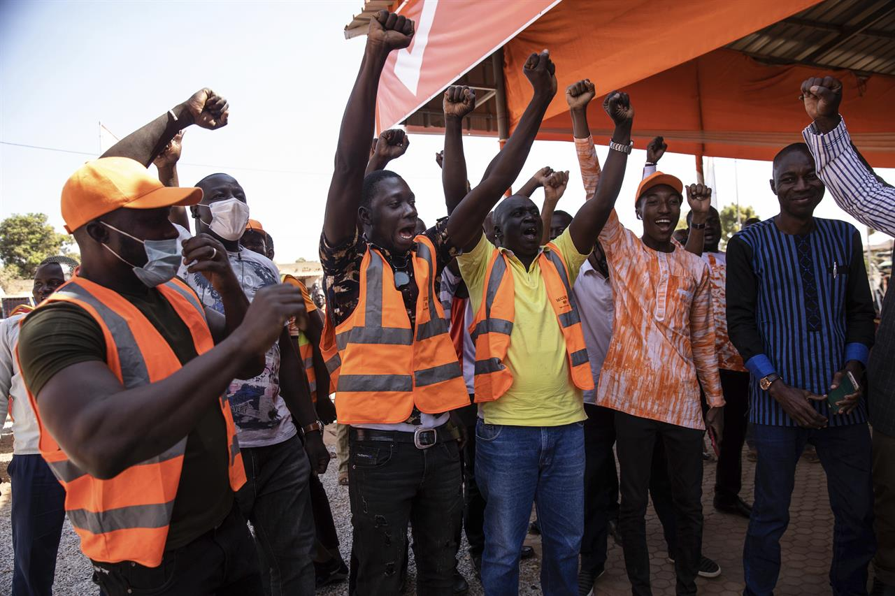 Supporters of President Roch Marc Christian Kabore celebrate in Ouagadougou as they learn he will serve another five years as Burkina Faso's president, according to provisional results announced by the National Independent Electoral Commission Thursday Nov 26, 2020. (AP Photo/Sophie Garcia)