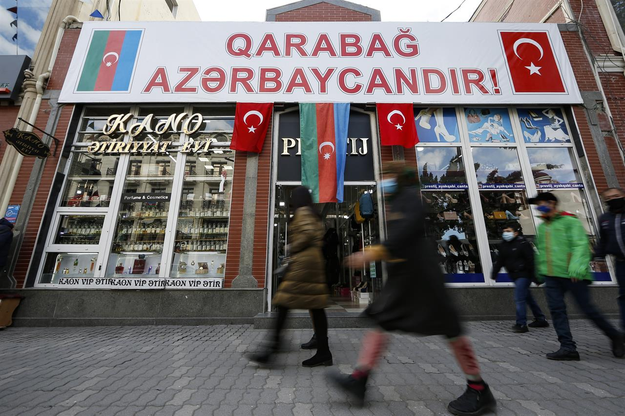 """People walk past a poster reading """"Karabakh is Azerbaijan"""" in Ganja, Azerbaijan's second largest city, near the border with Armenia, Azerbaijan, Thursday, Nov. 26, 2020. Azerbaijan's President Ilham Aliyev has vowed to rebuild and revive the Kalbajar region, which Armenian forces ceded in a truce that ended six weeks of intense fighting over Nagorno-Karabakh. (AP Photo/Emrah Gurel)"""
