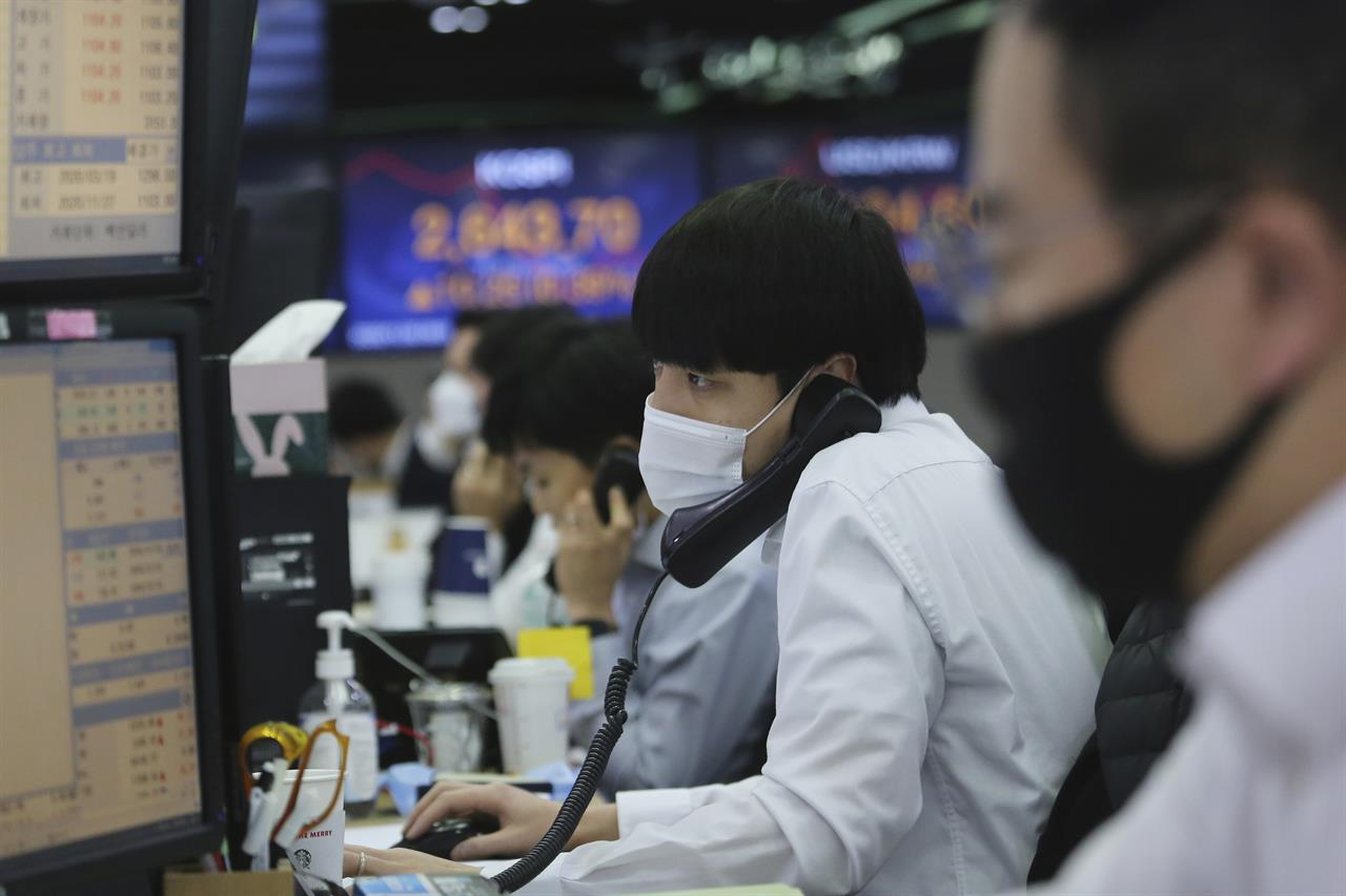 A currency trader watches monitors at the foreign exchange dealing room of the KEB Hana Bank headquarters in Seoul, South Korea, Monday, Nov. 30, 2020. Asian shares were mixed on Monday on renewed caution despite a record high finish on Wall Street last week driven by hopes for a COVID-19 vaccine and relief for the global economy. (AP Photo/Ahn Young-joon)