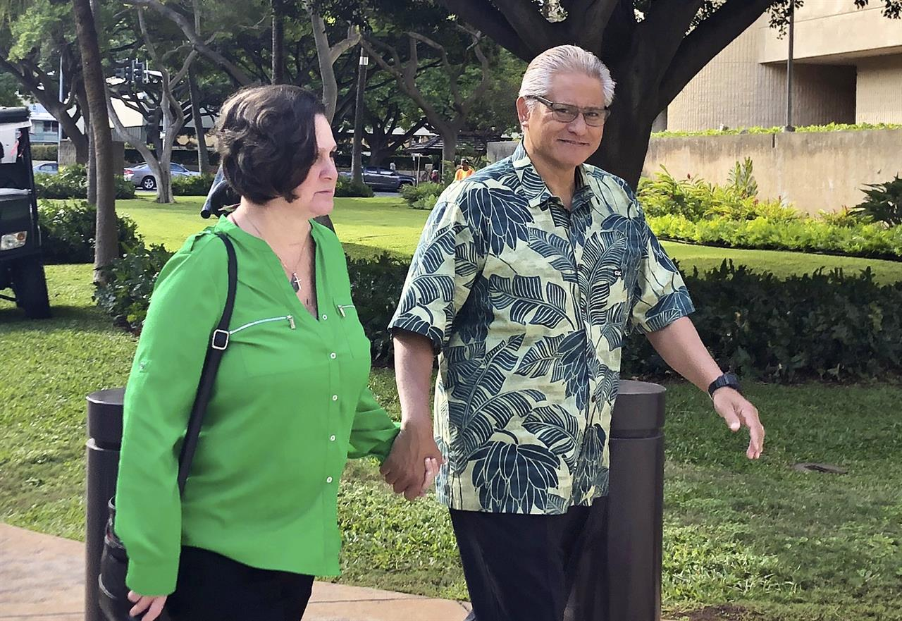FILE - In this March 12, 2019, file photo, retired Honolulu police chief Louis Kealoha and his wife, former deputy city prosecutor Katherine Kealoha, hold hands while walking to U.S. district court in Honolulu. A once-respected, now-estranged power couple are scheduled to be sentenced Monday, Nov. 30, 2020, in Hawaii's biggest corruption case. A jury convicted Katherine and Louis Kealoha of conspiracy in a plot to frame her uncle to keep him from revealing fraud that financed their fancy lives. (AP Photo/Jennifer Sinco Kelleher, File)