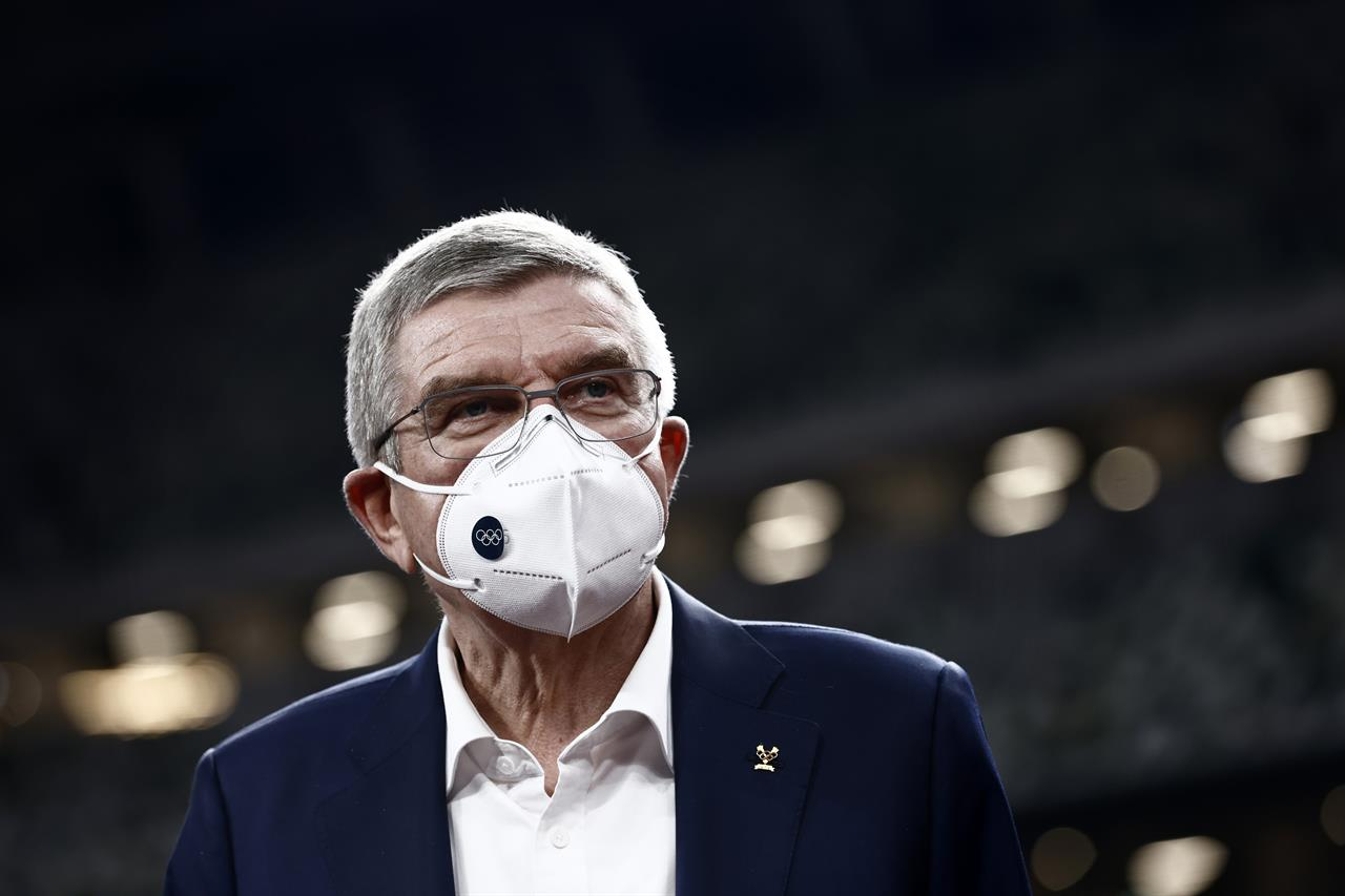 """IOC President Thomas Bach visits the National Stadium, the main venue for the 2020 Olympic and Paralympic Games postponed until July 2021 due to the coronavirus pandemic, in Tokyo Tuesday, Nov. 17, 2020. Bach said during this week's trip to Tokyo that he is """"encouraging"""" all Olympic """"participants"""" and fans to be vaccinated - if one becomes available - if they are going to attend next year's Tokyo Olympics. (Behrouz Mehri/Pool Photo via AP)"""