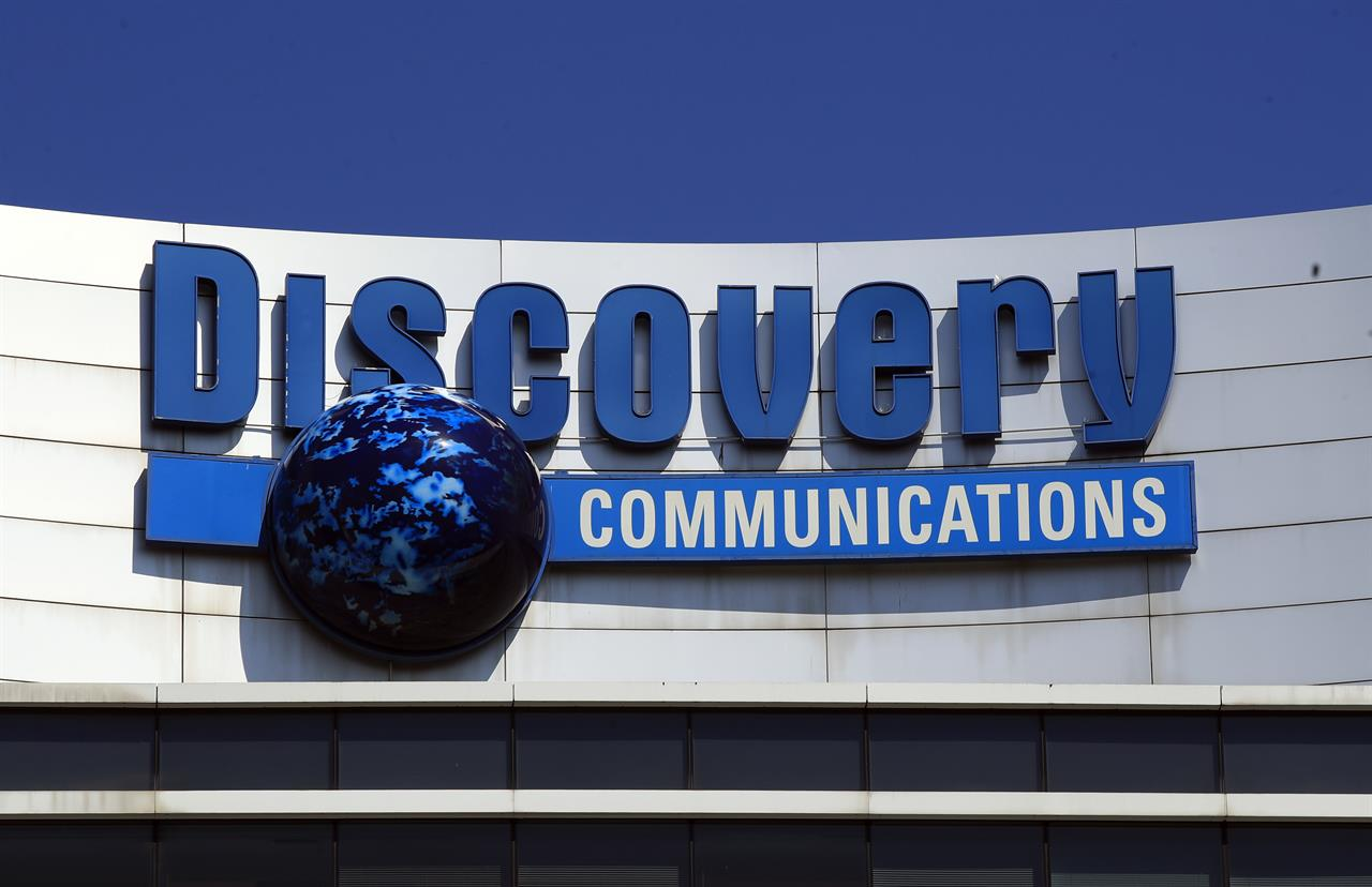 FILE - In this July 31, 2017, file photo, the Discovery Communications logo sits atop its headquarters in Silver Spring, Md. Discovery is joining the increasingly crowded streaming fray with its own reality-focused service Discovery Plus that will include shows from the Food Network, HGTV, TLC and its other networks. It launches Jan 4. (AP Photo/Manuel Balce Ceneta, File)