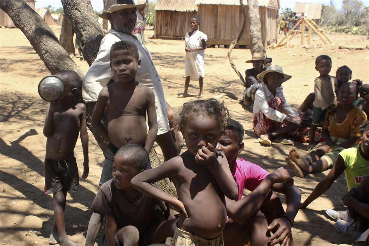 Children shelter from the sun in Ankilimarovahatsy, Madagascar,  a village in the far south of the island where most children are acutely malnourished, Monday, Nov. 9, 2020. As a consequence of three straight years of drought, along with historic neglect by the government of the remote region as well as the COVID-19 pandemic,1.5 million people are in need of emergency food assistance, according to the U.N. World Food Program. (AP Photo/Laetitia Began)