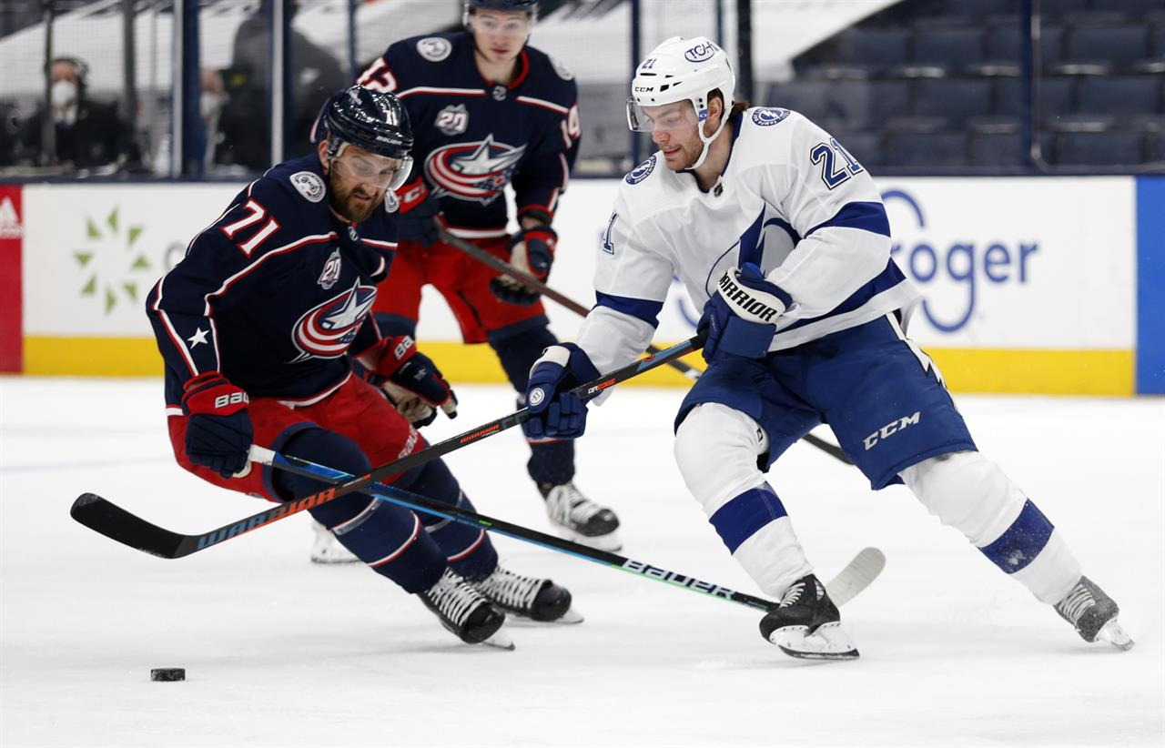Tampa Bay Lightning forward Brayden Point, right, reaches for the puck in front of Columbus Blue Jackets forward Nick Foligno during the first period an NHL hockey game in Columbus, Ohio, Thursday, April 8, 2021. (AP Photo/Paul Vernon)