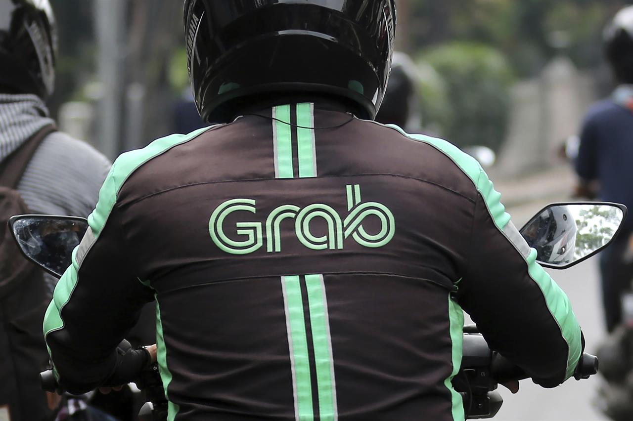 FILE - In this July 24, 2017, file photo, a GrabBike driver rides on his motorbike in Jakarta, Indonesia. Southeast Asia's largest ride-hailing company, Grab Holdings, said Tuesday, April 13, 2021 that it plans to merge with U.S.-based Altimeter Growth Capital in a deal that would value it at nearly $40 billion in preparation for an initial public offering in the U.S. (AP Photo/Tatan Syuflana, File)