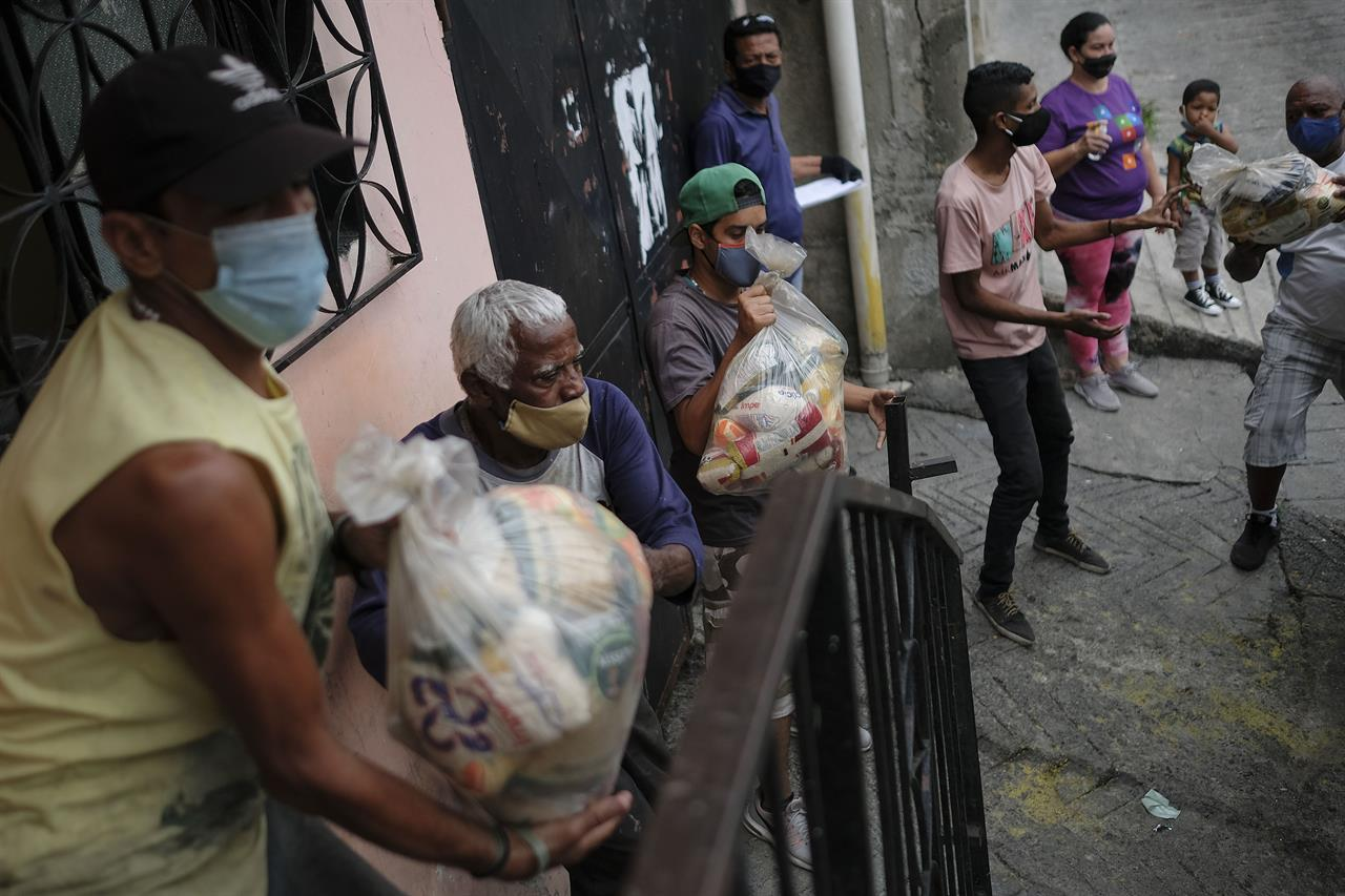Residents help to unload bags of basic food staples, such as pasta, sugar, flour and kitchen oil, provided by a government food assistance program, in the Santa Rosalia neighborhood of Caracas, Venezuela, Saturday, April 10, 2021. The program known as Local Committees of Supply and Production, CLAP, provides subsidized food for vulnerable families, especially now in the midst of a quarantine to stop the COVID-19 pandemic that has left many without income. (AP Photo/Matias Delacroix)