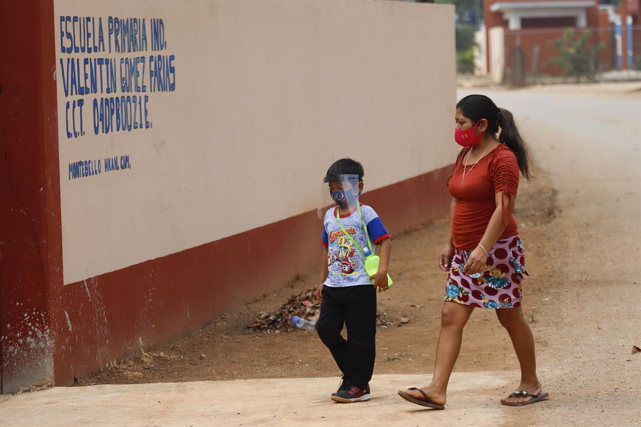 Wearing a mask to curb the spread of the new coronavirus, a mother walks her son to the first day of class at the Valentín Gomez Farias Indigenous Primary School in Montebello, Hecelchakan, Campeche state, Monday, April 19, 2021. Campeche is the first state to transition back to the classroom after a year of remote learning due to the pandemic. (AP Photo/Martin Zetina)