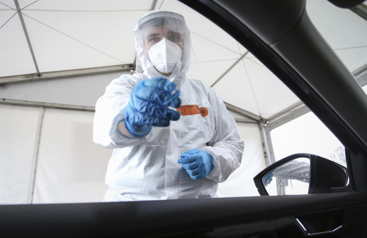 "A Corona Drive-In testing station employee stands next to an open car window to take a nasal swab in Osnabrueck, Germany, Monday, April 19, 2021. Appointments can be made online for testing. The result is communicated by email after a short waiting time. With the ""citizen test"", all residents of Germany have the opportunity to be tested for an infection with the Corona virus free of charge. (Friso Gentsch/dpa via AP)"