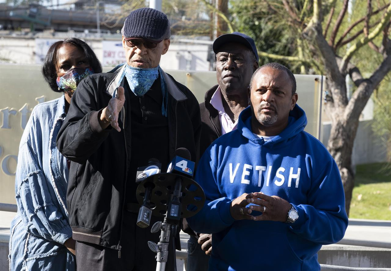 Civil rights activists Najee Ali, right and Los Angeles Urban Policy Roundtable President Earl Ofari Hutchinson address the media in front of the North Hollywood Police station in Los Angeles on Saturday, Jan. 2, 2021. They are calling for LAPD Chief Michel Moore to order the immediate arrest of the woman who they say lives in Los Angeles, and has reportedly been identified by NYPD sources as the woman caught on camera falsely accusing the 14-year-old son of jazz trumpeter Keyon Harrold of stealing her iPhone at a New York Hotel. New York Police have released a new video clip showing the woman trying to tackle the boy after falsely accusing him of stealing her phone at a New York City hotel. (AP Photo/Richard Vogel)