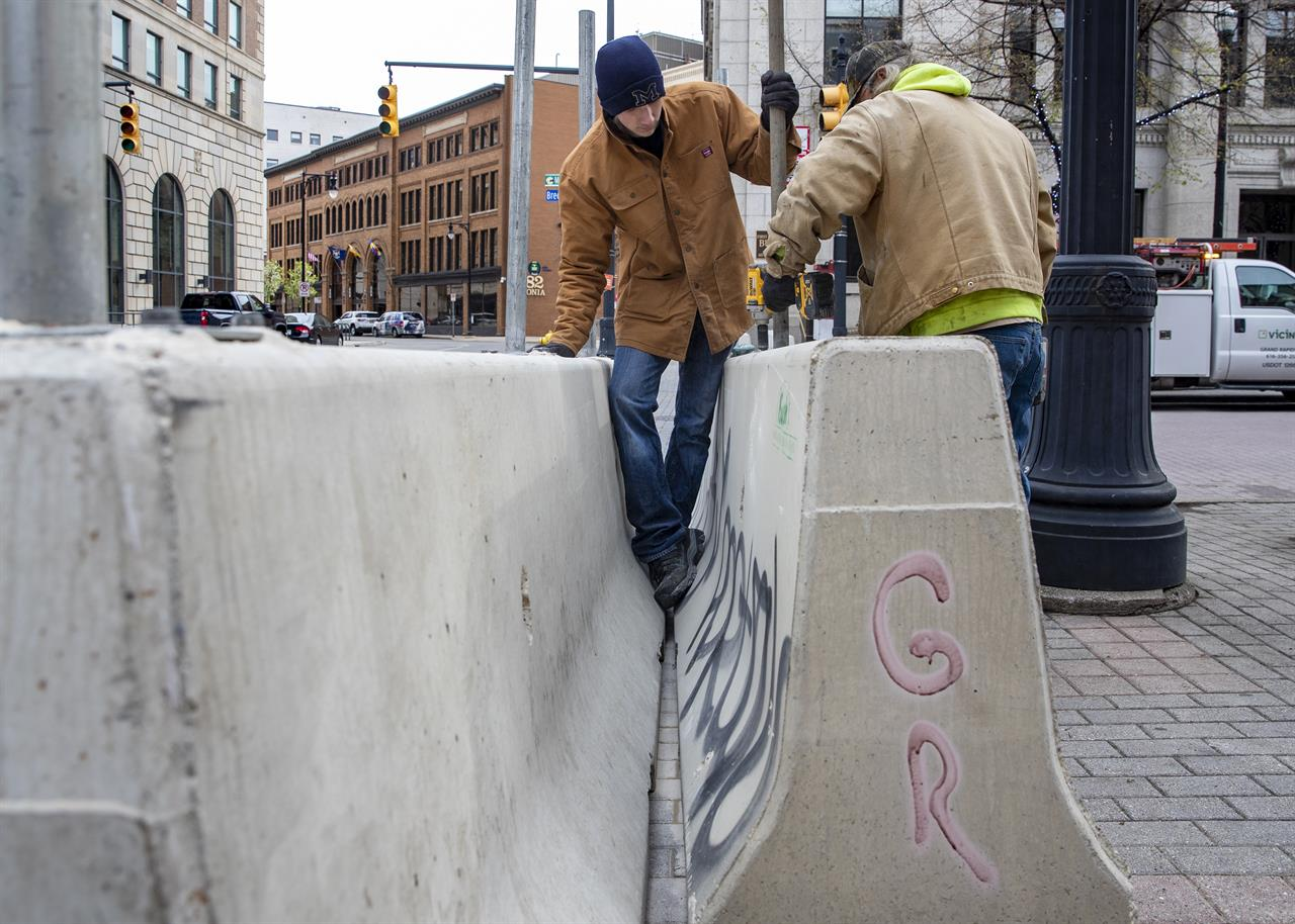 Cole Bond, left, and Mike Jack, from Fence Consultants of West Michigan, put up barricades in downtown Grand Rapids, Mich., Tuesday, April 20, 2021, as a jury deliberates fate of Derek Chauvin in death of George Floyd. Grand Rapids had some of Michigan's worst violence last May after the death of Floyd.  (Cory Morse/MLive.com/The Grand Rapids Press via AP)