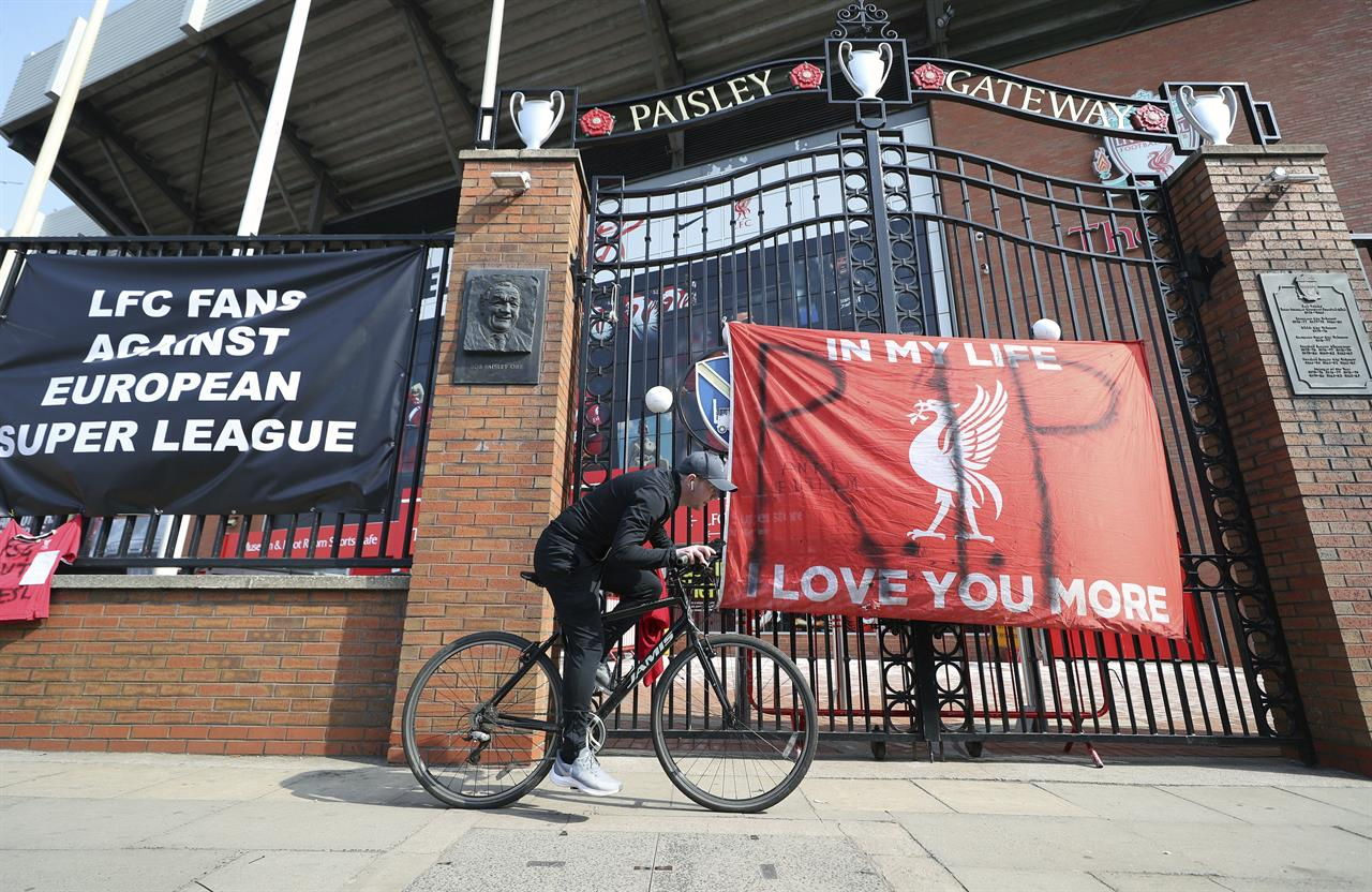 A man cycles past banners outside of Anfield Stadium, Liverpool, England protesting against the clubs decision to join the European Super Leaguer, Tuesday April 20, 2021. Chelsea and Manchester City are preparing to dramatically abandon plans to join a breakaway Super League threatening to implode the project by a group of elite English, Spanish and Italian clubs less than two days after it was announced.  (Peter Byrne/PA via AP)