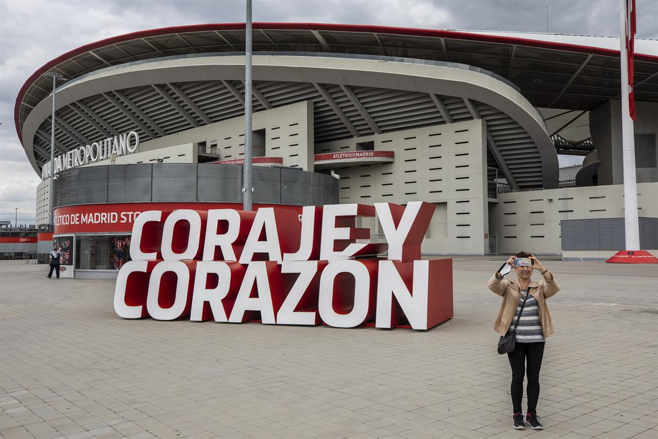 "A woman takes a snapshot in front Atletico Madrid's Wanda Metropolitano stadium in Madrid, Spain, Tuesday, April 20, 2021. A group of 12 elite English, Spanish and Italian clubs dramatically split European soccer on Sunday by announcing the formation of a largely-closed Super League. The Super League's founding chairman Florentino Perez on Tuesday, April 20, 2021 says the competition is being created to save soccer for everyone and not to make the rich clubs richer. The Real Madrid president says it's ""impossible"" that players from the participating teams will be banned by UEFA. (AP Photo/Bernat Armangue)"