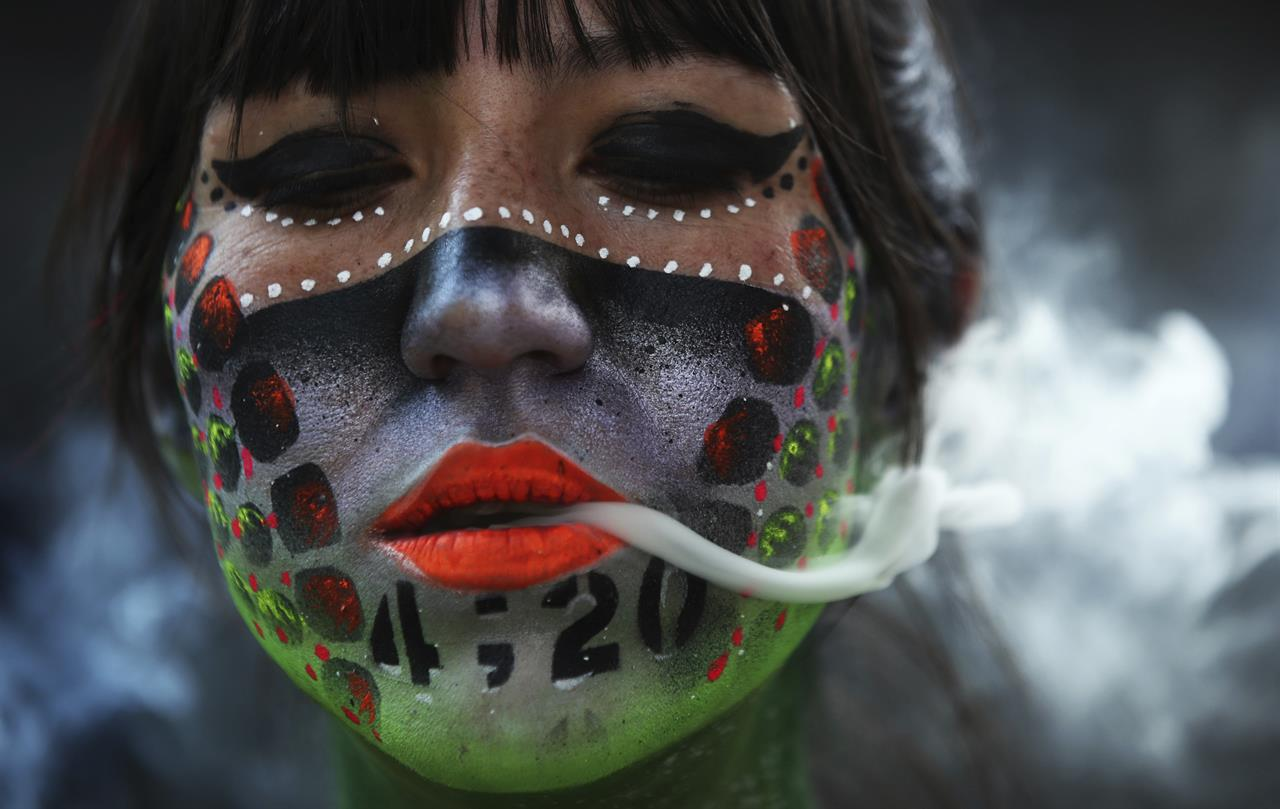 "Ana Mendez Casteñeda smokes marijuana during ""Fumaton 420"" outside the national Senate in Mexico City, Tuesday, April 20, 2021. The demonstrators are calling for the legalization of marijuana. (AP Photo/Marco Ugarte)"