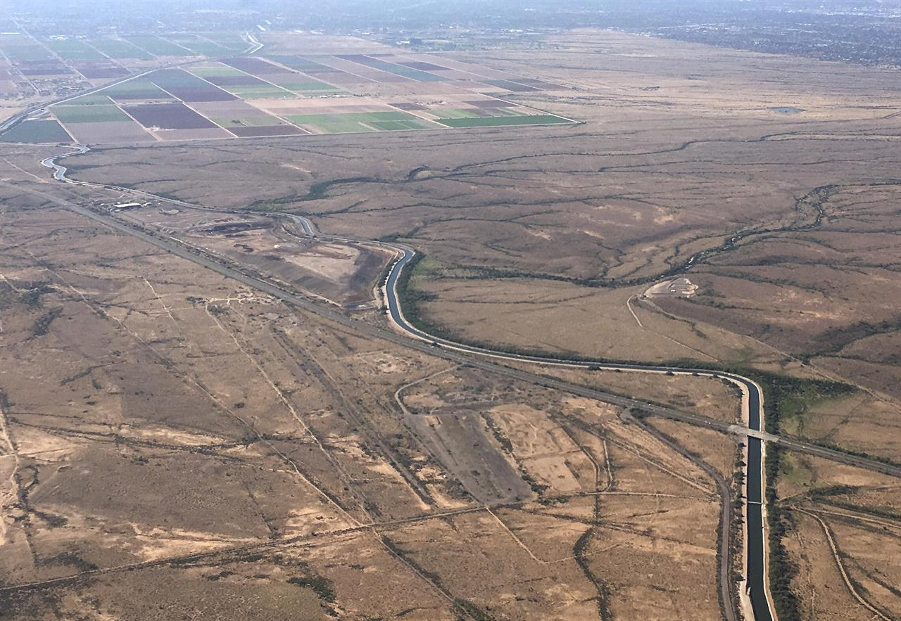 FILE - In this Oct. 8, 2019, file photo, the Central Arizona Project canal runs through rural desert near Phoenix. Water officials in Arizona say they are prepared to lose about one-fifth of the water the state gets from the Colorado River in what could be the first federally declared shortage in the river that supplies millions of people in the U.S. West and Mexico. The voluntary and mandatory Tier 1 cuts mean Arizona will lose 18% of its Colorado River supply, or 512,000 acre-feet of water. The amount represents 30% of the water that goes to the Central Arizona Project, which manages the canal system and had made excess water available for farmers. (AP Photo/Ross D. Franklin, File)