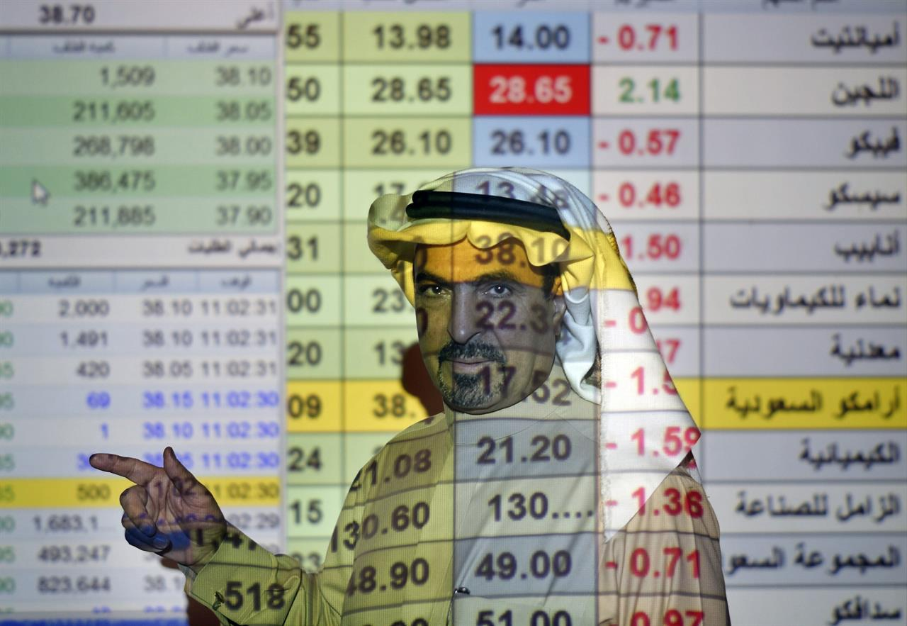 FILE- In this Dec. 12, 2019, file photo, a trader talks to others in front of a screen displaying Saudi stock market values at the Arab National Bank in Riyadh, Saudi Arabia. Saudi Aramco said Tuesday, May 4, 2021, it's profits soared by 30% for the first-quarter of the year, compared to last year, riding on the back of higher crude oil prices as some of the world's biggest economies claw their way out of recession and ease restrictions amid vaccine roll-outs against COVID-19.(AP Photo/Amr Nabil, File)