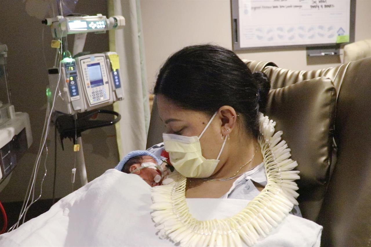 """In this undated photo provided by Hawaii Pacific Health, Lavinia """"Lavi"""" Mounga holds her son Raymond Mounga at Kapiolani Medical Center for Women & Children in Honolulu. Mounga had no idea the baby was coming when she went into labor on a flight from her home in Utah to Honolulu the week before. """"I just didn't know I was pregnant, and then this guy just came out of nowhere,"""" Mounga said during a video interview with Hawaii Pacific Health. The baby boy arrived early at just 29 weeks while mom was traveling to Hawaii for vacation with her family. (Taylor Ursulum/Hawaii Pacific Health via AP)"""