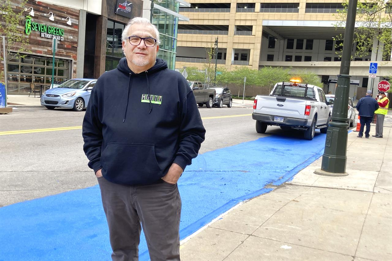 Tony Sacco, co-owner of Mootz Pizzeria and Bar in Detroit, stands on Library Street near his restaurant Wednesday, May 5, 2021. Sacco painted a portion of the street blue to clear up confusion about parking in a handicap zone that only has a single handicap sign. Sacco said it's confusing because parking enforcers consider the space reserved for as many as four vehicles. A city traffic engineer told Sacco that more signs will be installed but the blue paint will be removed. (AP Photo/Ed White)