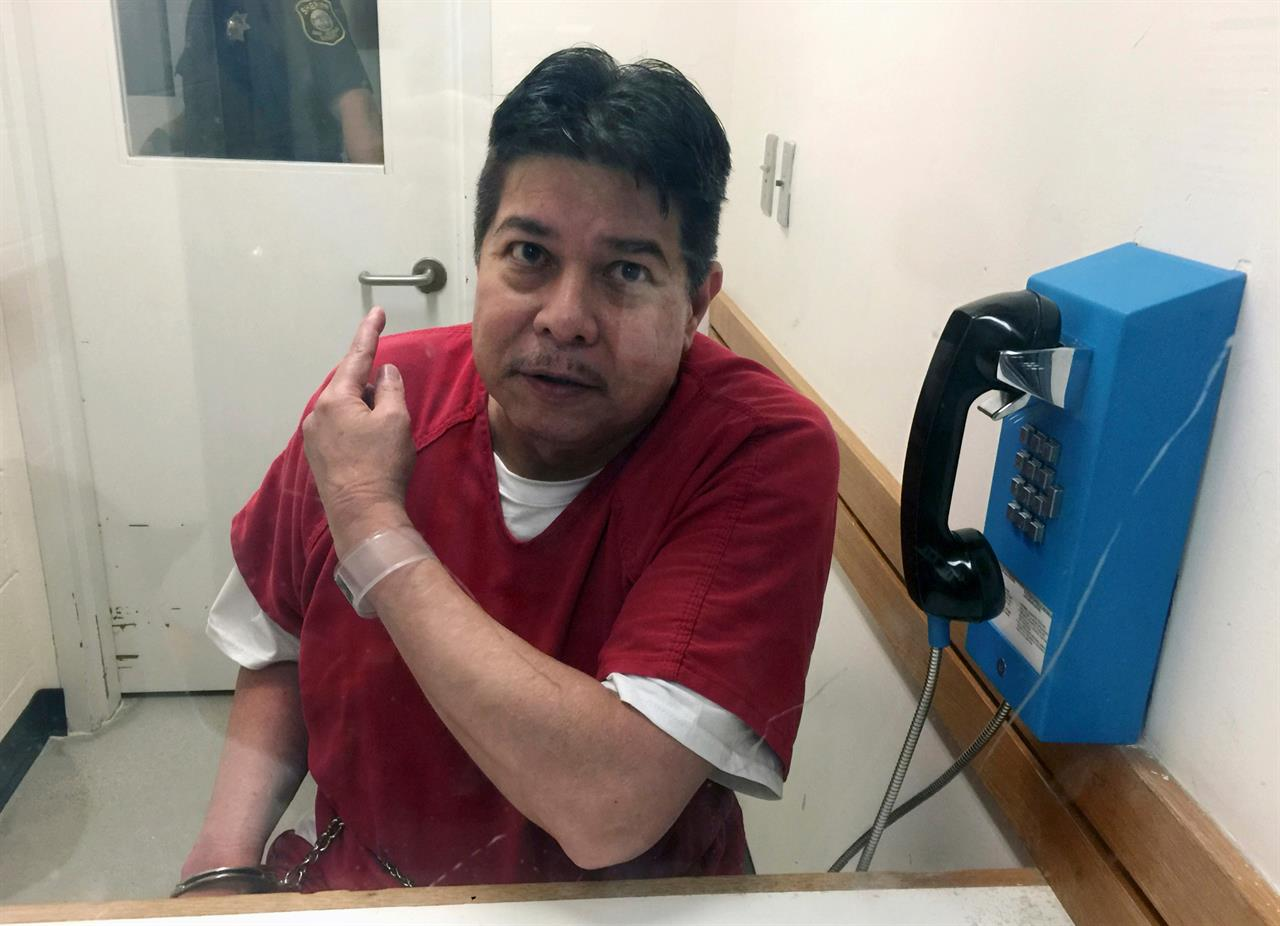 FILE - In this Nov. 17, 2017, file photo, escaped hospital patient Randall Saito points to a guard as he sits in an inmate visitor's booth at San Joaquin County Jail before a scheduled court hearing in French Camp, Calif. Saito spent decades in a Hawaii psychiatric hospital for killing a woman and was sentenced to five years in prison Thursday, May 6, 2021, for escaping from the facility in 2017 and flying to California before he was captured. (AP Photo/Terry Chea, File)