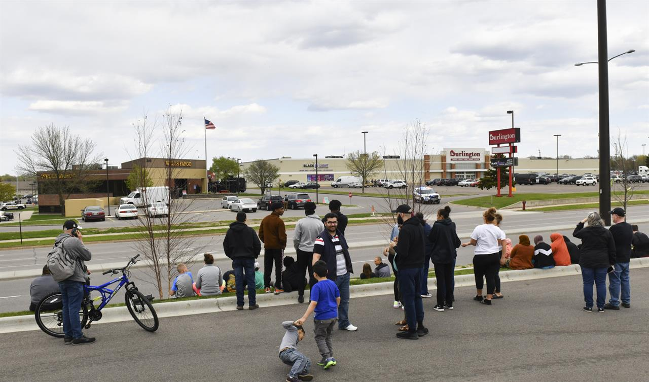 People gather in a nearby parking lot as officers surround the Wells Fargo branch Thursday May 6, 2021, in south St. Cloud, Minn. Police in Minnesota were on the scene Thursday of a reported bank robbery with hostages. (Dave Schwarz/St. Cloud Times via AP)