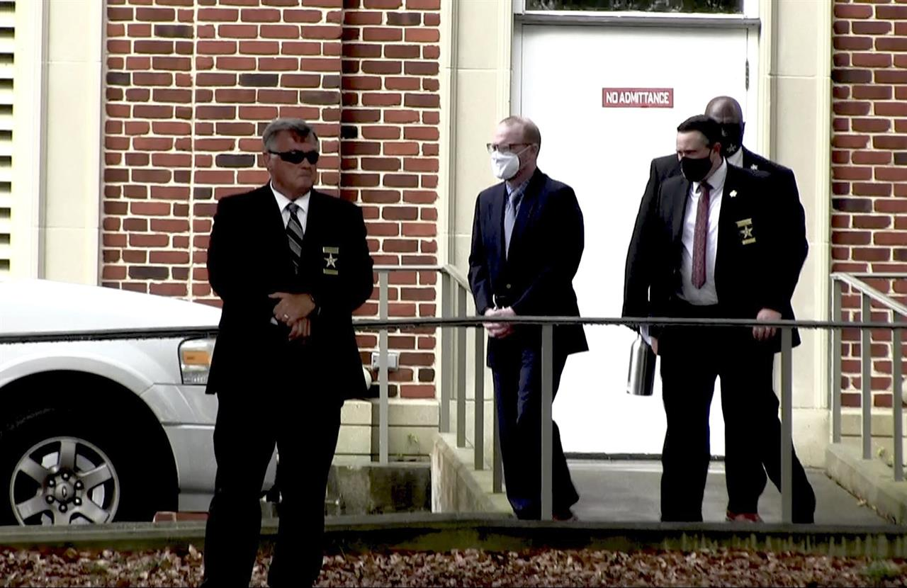 In this image from video, Travis McMichael, center, accused in the shooting death of Ahmaud Arbery, is led by security officers from the Glynn County Courthouse in Brunswick, Ga., Wednesday, May 12, 2021. A Georgia judge will continue hearing legal motions Thursday in the murder case of three men facing a fall trial in the slaying of Ahmaud Arbery, a Black man who was chased and shot after being spotted running in the defendants' neighborhood. (AP Photo/Lewis M. Levine)