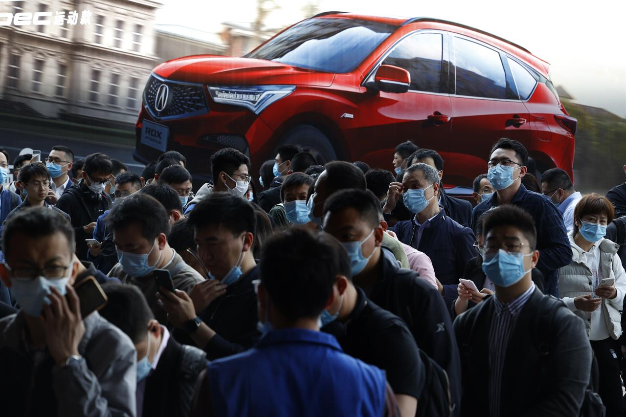 FILE - In this April 21, 2021, file photo, visitors attend the Shanghai Auto Show in Shanghai. The United Nations has responded to the rebounding Chinese and U.S. economies by revising its global economic forecast upward to 5.4% for 2021. But it warned that surging COVID-19 cases and inadequate availability of vaccines in many countries threaten a broad-based recovery.  (AP Photo/Ng Han Guan, File)