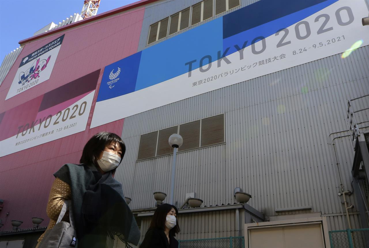 FILE - In this Feb. 24, 2021, file photo, people walk past posters to promote the Olympic Games scheduled to start in the summer in Tokyo. Frustration is mounting over Japanese Prime Minister Yoshihide Suga's request that people cooperate while he pushes to hold the Olympics in just over two months. (AP Photo/Koji Sasahara, File)