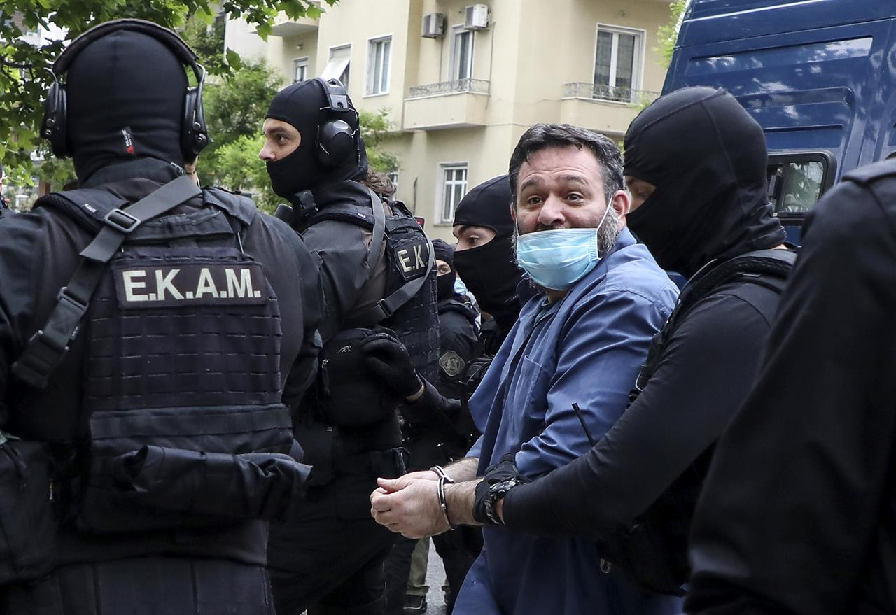 European Parliament member Ioannis Lagos is transferred to the Greek Police headquarters, in Athens, Saturday, May 15, 2021. Lagos arrived in Greece Saturday to serve a 13-year sentence imposed on him last October for being a leading member of the extreme-right Golden Dawn party, which was labeled a criminal organization. (Stelios Stefanou/InTime News via AP)