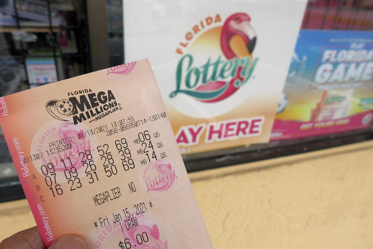 FILE - In this Wednesday, Jan. 13, 2021, file photo, a customer shows off a Mega Millions lottery ticket after purchasing it, in Orlando, Fla. The nation's two national lottery games are designed to produce immense jackpots that generate huge sales, and the recipe certainly is working now as prizes on Thursday reached a combined $1.39 billion. The next drawing for Mega Millions is Friday night, when a $750 million prize will be up for grabs. (AP Photo/John Raoux, File)