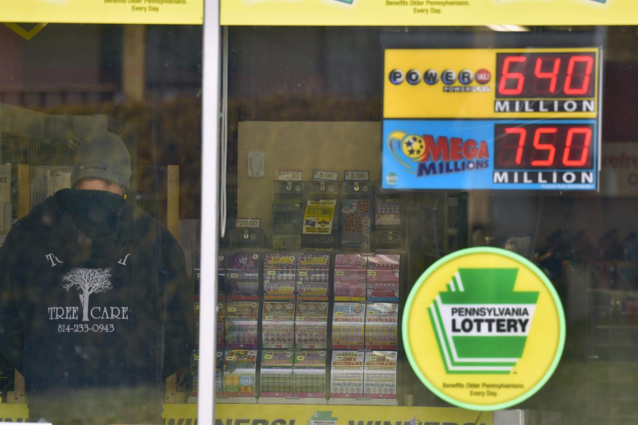 A lottery customer purchases lottery tickets at Conjelko's Dairy Store in Windber, Pa., as the Mega Millions grew to $750 million and the PowerBall to $ 640 Million on Thursday, Jan. 14, 2021. (Todd Berkey/The Tribune-Democrat via AP)