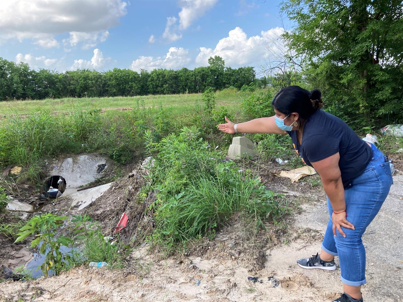 Shirley Ronquillo, a Houston area community activist,points to an open drainage ditch that is blocked by debris and trash on May 27, 2021, in Houston. The ditch, which should remain unobstructed, is located near a subdivision in an unincorporated part of Harris County that has a long history of flooding. (AP Photo/Juan A. Lozano)