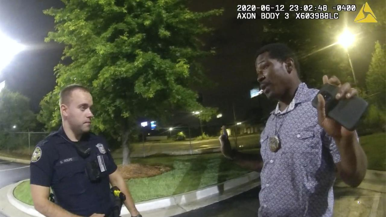 FILE - In this June 12, 2020, file photo from a screen grab taken from body camera video provided by the Atlanta Police Department Rayshard Brooks, right, speaks with Officer Garrett Rolfe, left, in the parking lot of a Wendy's restaurant, in Atlanta. A judge on Friday, June 4, 2021 granted a request from the district attorney in Atlanta to recuse her office from prosecuting the police officer who fatally shot Rayshard Brooks and instructed the state attorney general to appoint another prosecutor. (Atlanta Police Department via AP, File)