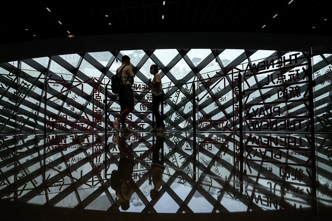 A couple wearing face masks to help curb the spread of the coronavirus is silhouetted as they chat each other at a shopping mall in Beijing, Sunday, June 6, 2021. (AP Photo/Andy Wong)