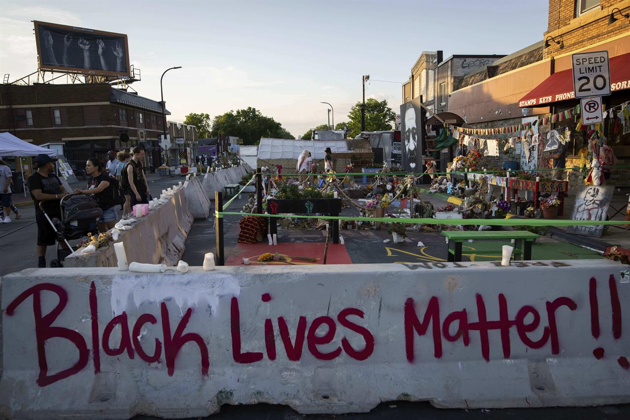 Jersey barriers placed by the city of Minneapolis surround memorials as community members gather in George Floyd Square to demand justice for Winston Boogie Smith Jr., on Monday, June 7, 2021. Smith was fatally shot by members of a U.S. Marshals task force. (AP Photo/Christian Monterrosa)