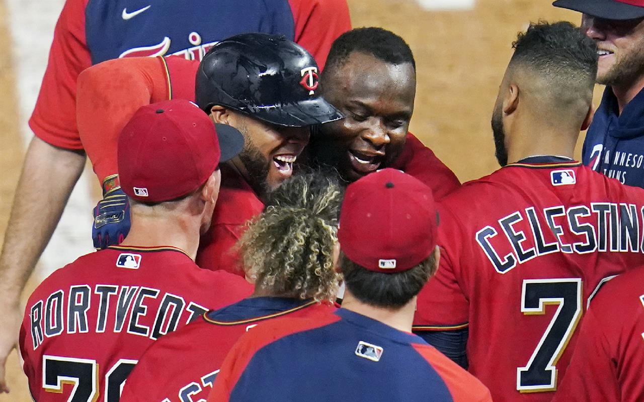 Minnesota Twins' Miguel Sano, center hugs Nelson Cruz after Cruz's two-run home run off New York Yankees relief pitcher Aroldis Chapman during the ninth inning of a baseball game Thursday, June 10, 2021, in Minneapolis. The Twins won 7-5. (AP Photo/Jim Mone)