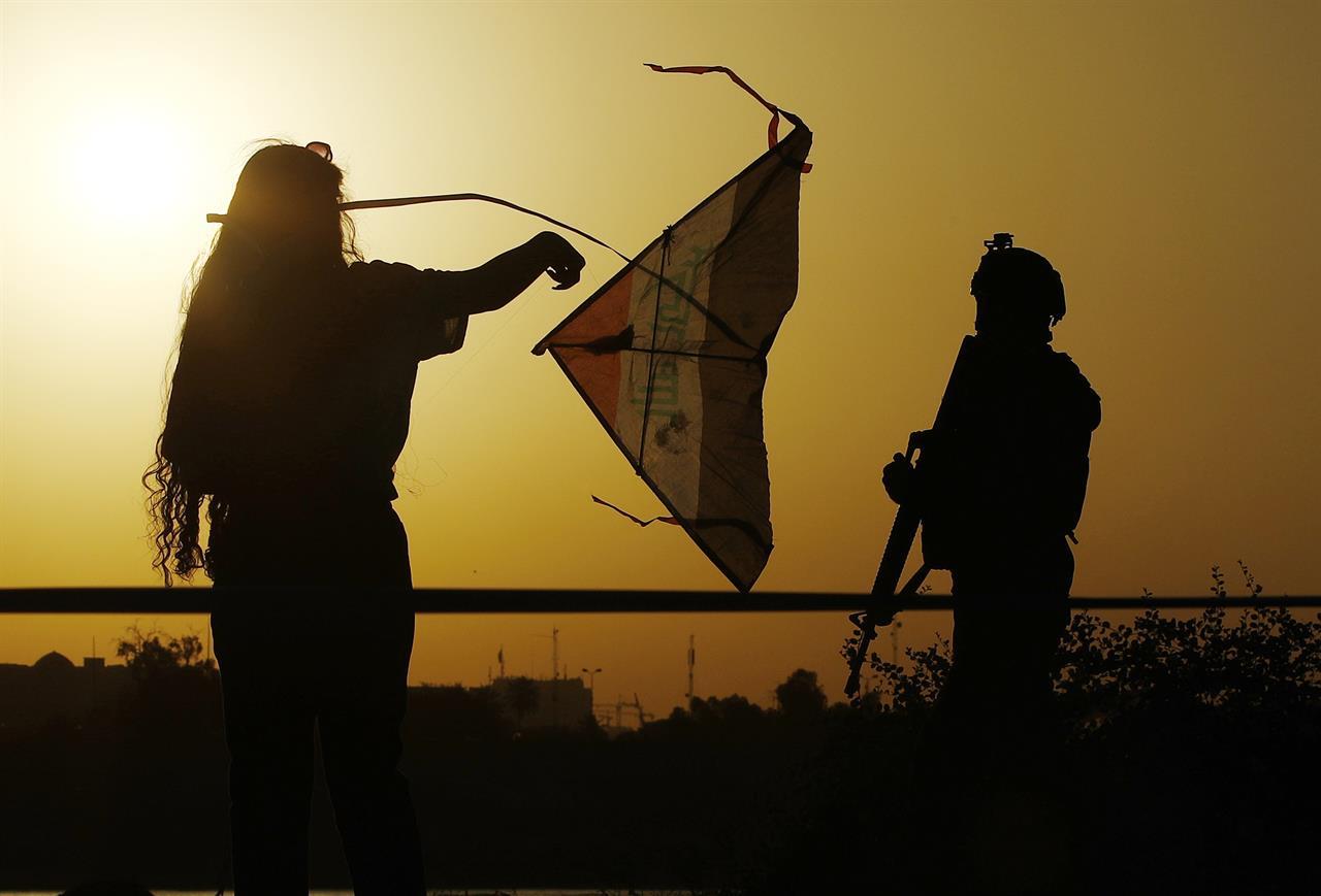 People take part in the Baghdad Kite Festival as the sun sets in Baghdad, Iraq, Saturday, June 5, 2021. (AP Photo/Hadi Mizban)