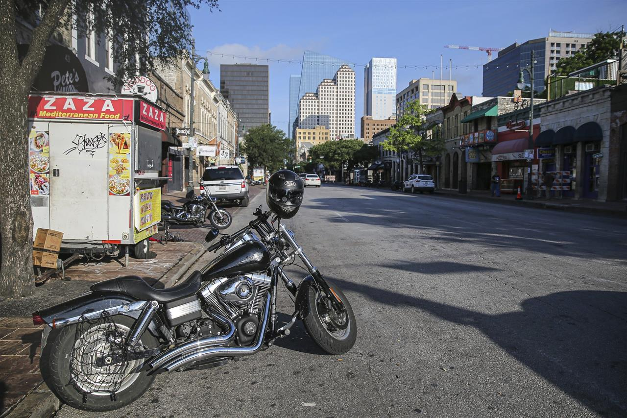 Some abandoned bikes are parked on the streets after a early morning shooting on Saturday, June 12, 2021 in downtown Austin, Texas. Authorities say someone opened fire on the busy entertainment district wounding several people before getting away.  (Aaron Martinez/Austin American-Statesman via AP)