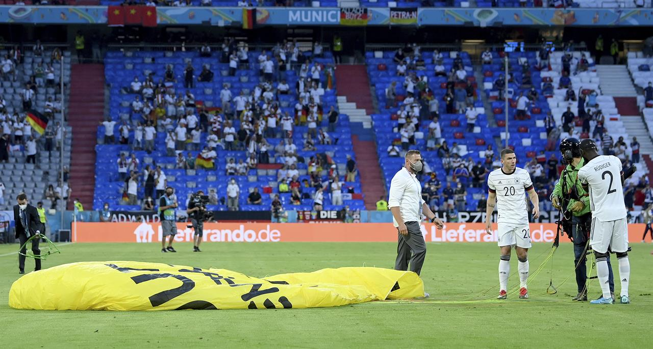Germany's Antonio Ruediger, right, and Germany's Robin Gosens speak to a protestor who landed on the pitch before the Euro 2020 soccer championship group F match between France and Germany at the Allianz Arena stadium in Munich, Tuesday, June 15, 2021. (Matthias Hangst/Pool via AP)