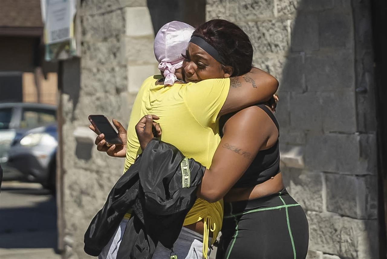 A woman  receives a hug from a supporter outside the scene of a shooting outside a home in Chicago, Tuesday, June 15, 2021.   Police say an argument at a house on Chicago's South Side erupted in fatal gunfire, leaving some dead and others injured. (Ashlee Rezin Garcia /Chicago Sun-Times via AP)